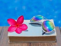 Libro ed occhiali da sole, fondo dell'acqua blu, Fotografia Stock Libera da Diritti