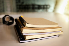 Libro ed orologio sulla tavola di legno con luce solare, spazio della copia fotografie stock