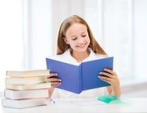 Libro el estudiar y de lectura de la muchacha en la escuela Imágenes de archivo libres de regalías