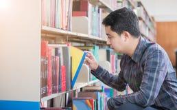 Libro elegante del hallazgo del estudiante en el estante en biblioteca fotos de archivo