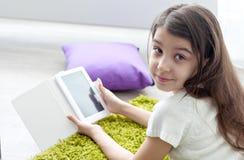 Libro elettronico della lettura della bambina mentre trovandosi sul pavimento Fotografia Stock Libera da Diritti
