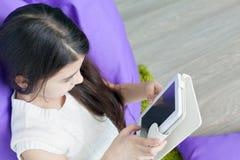 Libro elettronico della lettura della bambina nella stanza Fotografia Stock