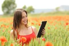 Libro elettronico della lettura della donna in un campo rosso Fotografia Stock Libera da Diritti