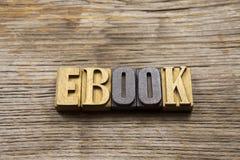 Libro elettronico in di legno composto su un fondo rustico Immagine Stock