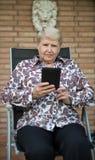 Libro elettronico senior della lettura della donna fotografie stock