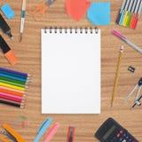 Libro en blanco del bosquejo y herramientas coloridas de la escuela en el fondo de madera Imagen de archivo libre de regalías