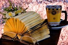 Libro en el fondo de una taza de flores del café El libro es una fuente de trabajo importante del conocimiento, literario o cient fotos de archivo