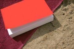 Libro en la playa con la toalla Fotos de archivo