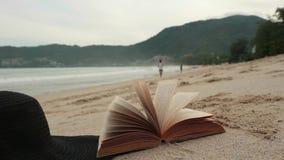 Libro en un arena de mar en la página de torneado de la playa con el viento metrajes
