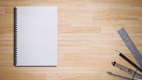 Libro espiral con la pluma, el lápiz, la regla y el compás fotos de archivo