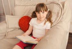 Libro felice del briciolo della bambina nelle mani Fotografia Stock Libera da Diritti