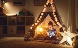 Libro feliz de la risa y de lectura de la muchacha del niño en oscuridad en tienda en ho Imagen de archivo libre de regalías