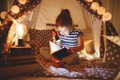 Libro feliz de la risa y de lectura de la muchacha del niño en oscuridad en tienda en ho Imagenes de archivo