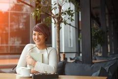 Libro feliz del abarcamiento de la muchacha en café Foto de archivo libre de regalías