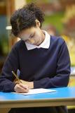 Libro femminile di scrittura dell'allievo della scuola elementare in aula Fotografia Stock