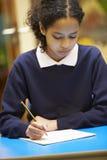 Libro femminile di scrittura dell'allievo della scuola elementare in aula Immagini Stock Libere da Diritti