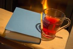 Libro, golpe del té y chimenea Imagenes de archivo
