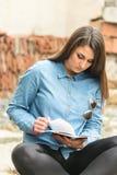 Libro hermoso de la sentada y de lectura del adolescente en el lugar rústico Fotografía de archivo