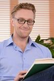 Libro interesante. Hombres alegres jovenes en vidrios que leen un libro Imagenes de archivo