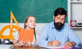 Libro interessante Di nuovo al banco Insegnamento privato Lezione privata piccolo bambino della ragazza con l'uomo barbuto dell'i fotografie stock libere da diritti