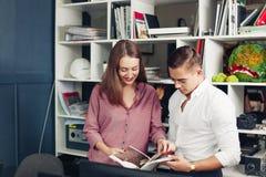 Libro internazionale maschio della lettura di due studenti su desidn insieme Immagini Stock Libere da Diritti