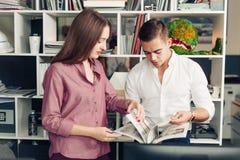 Libro internazionale maschio della lettura di due studenti su desidn insieme Fotografia Stock