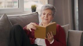 Libro jubilado feliz de la ficción de la lectura de la mujer que se relaja en sala de estar metrajes