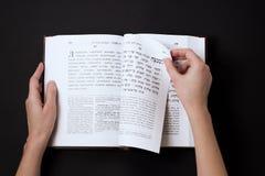 Libro judío, con la mano del ` s de la mujer, en fondo negro Texto del hebreo, rezo Libro de lectura de la mujer Fotografía de archivo libre de regalías