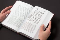 Libro judío, con la mano del ` s de la mujer, en fondo negro Texto del hebreo, rezo Libro de lectura de la mujer Imagen de archivo libre de regalías