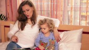 Libro lindo del cuento de la lectura de la niña pequeña con la mujer de la niñera de la niñera que se sienta en cama almacen de metraje de vídeo