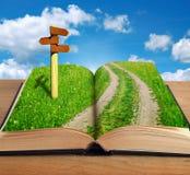 Libro mágico con el interior y el poste indicador del camino Fotografía de archivo