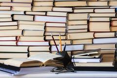Libro, manuale e vetri in biblioteca, mucchi di archivio del testo della letteratura, scaffali per libri della pila nel fondo f d fotografia stock
