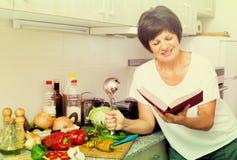 Libro maturo del cuoco della donna fotografie stock