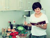 Libro maturo del cuoco della donna immagine stock libera da diritti
