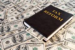 Libro nero e soldi con la riforma fiscale dell'iscrizione sul fondo delle banconote del dollaro immagine stock libera da diritti