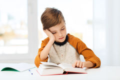 Libro o libro de texto de lectura del muchacho del estudiante en casa Imágenes de archivo libres de regalías