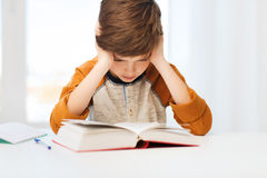 Libro o manuale di lettura del ragazzo dello studente a casa Immagine Stock
