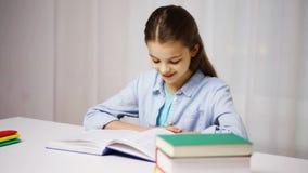 Libro o manuale di lettura felice della ragazza della scuola a casa stock footage