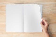 Libro o riviste in bianco aperto della mano immagine stock