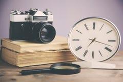 Libro, orologio e macchina fotografica immagine stock