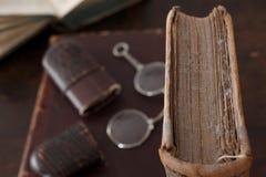 Libro polvoriento viejo con los vidrios de lectura Foto de archivo libre de regalías