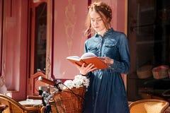 Libro premuroso del readng della donna e sognare sul beanch all'aperto fotografia stock libera da diritti