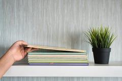 Libro puesto mano en el estante blanco - consiga organizado imagen de archivo libre de regalías