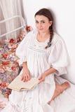 Libro rojo de la mujer en una cama Foto de archivo