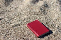 Libro rojo en la arena en un fondo borroso, arena en el libro, granos de la arena en un libro Foto de archivo libre de regalías