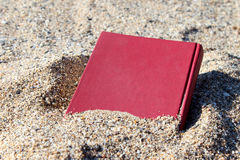 Libro rojo en la arena en un fondo borroso, cubierto con la arena, enterrada en la arena Imagenes de archivo