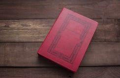 Libro rosso chiuso sulla tavola di legno immagine stock