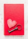 Libro rosso del diario con la chiave dell'annata e del cuore su fondo di legno bianco, vista superiore Scheda di giorno dei bigli Fotografia Stock