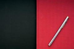 Libro rosso luminoso su una priorità bassa nera Fotografie Stock