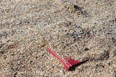 Libro rosso sulla sabbia su un fondo confuso, coperto di sabbia Immagine Stock